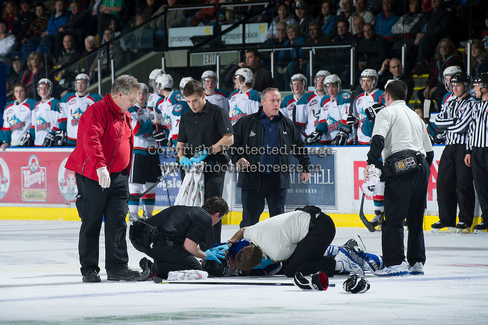 KELOWNA, CANADA - JANUARY 2:  Jeff Thorburn, athletic therapist of the Kelowna Rockets assists Khore Elliott, athletic therapist of the Victoria Royals as they tend to an injured Ben Walker #10 of the Victoria Royals as Kelowna Rockets team physician, Dr. Mike Shepherd enters the ice at the Kelowna Rockets on January 2, 2013 at Prospera Place in Kelowna, British Columbia, Canada (Photo by Marissa Baecker/Shoot the Breeze) *** Local Caption ***