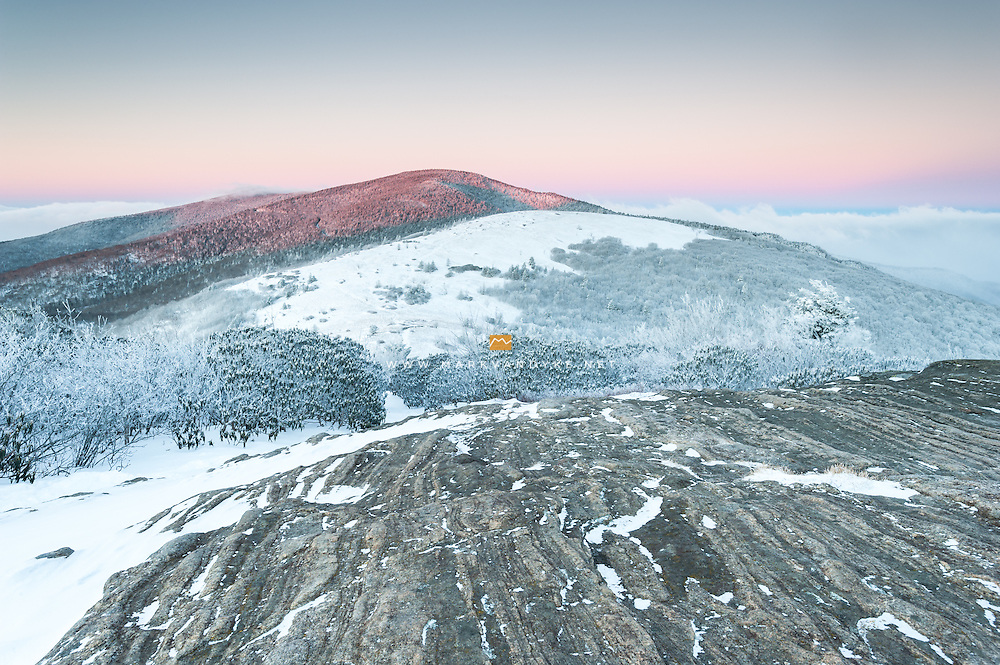 The first light of morning strikes Roan High Knob after a winter storm drops several inches of snow on the Roan Highlands.  Roan Mountain is located in Eastern Tennessee where visitors can pick up the Appalachian Trail and traverse a series of highland meadows with beautiful views.