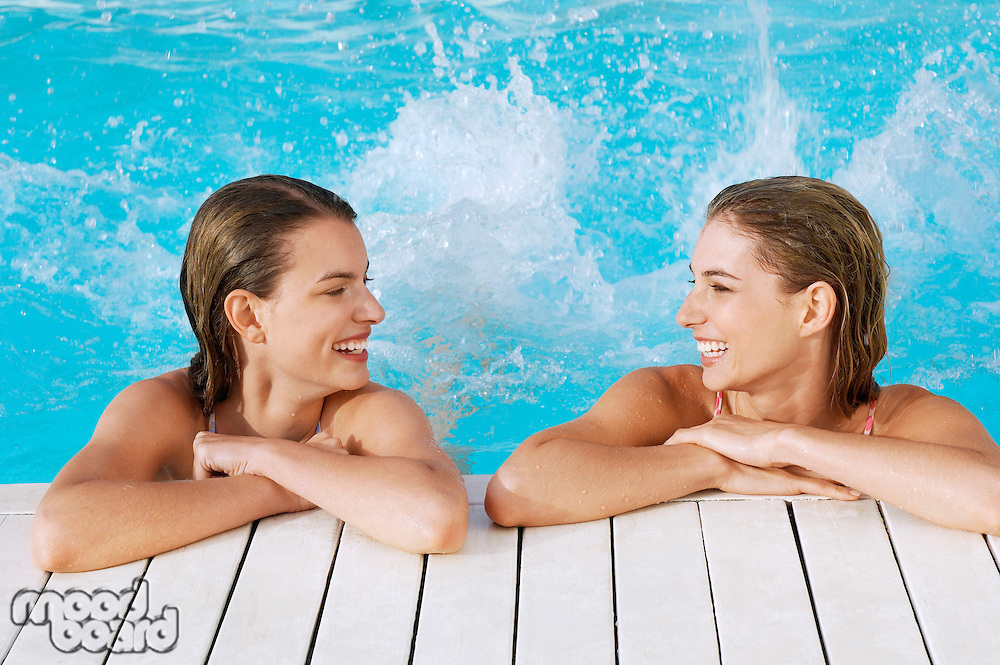 Two young women in pool at poolside splashing feet front view