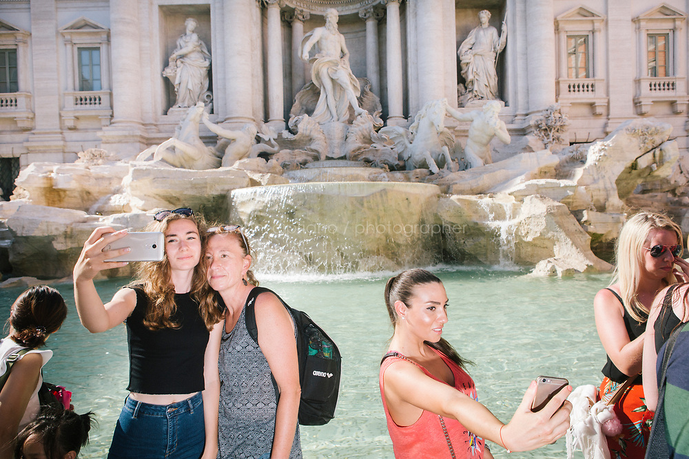 ROME, ITALY - 20 JUNE 2017: Tourists take selfies in front of the Trevi Fountain in Rome, Italy, on June 20th 2017.<br /> <br /> The warm weather has brought a menacing whiff of tourists behaving badly in Rome. On April 12, a man went skinny-dipping in the Trevi fountain resulting in a viral web video and a 500 euro fine.<br /> <br /> Virginia Raggi, the mayor of Rome and a national figurehead of the anti-establishment Five Star Movement,  issued an ordinance involving harsher fines for eating, drinking or sitting on the fountains, for washing animals or clothes in the fountain water or for throwing anything other than coins into the water of the Trevi Fountain, Bernini&rsquo;s Four Fountains and 35 other city fountains of artistic or historic significance around the city.  &ldquo;It is unacceptable that someone use them to go swimming or clean themselves, it&rsquo;s an historic patrimony that we must safeguard,&rdquo; Ms. Raggi said.