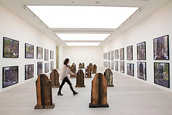 © Licensed to London News Pictures. 19/11/2013. London, UK. A Saatchi Gallery employee walks through 'Markers' (2011), a series of gravestones made from reclaimed timber by American artist Marianne Vitale, at the press view for 'Body Language' a new exhibition at the gallery in London today (19/11/2013). Focussing on the human form, the exhibition features the work of 19 emerging international artists and opens to the public on the 20th of November 2013. Photo credit: Matt Cetti-Roberts/LNP
