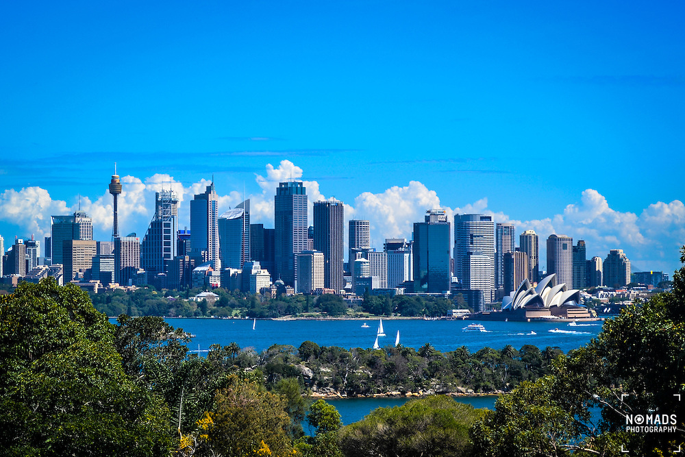 Sydney skyline as seen from Taronga Zoo. Located on Australia's east coast, the metropolis surrounds the world's largest natural harbour, and sprawls towards the Blue Mountains to the west.