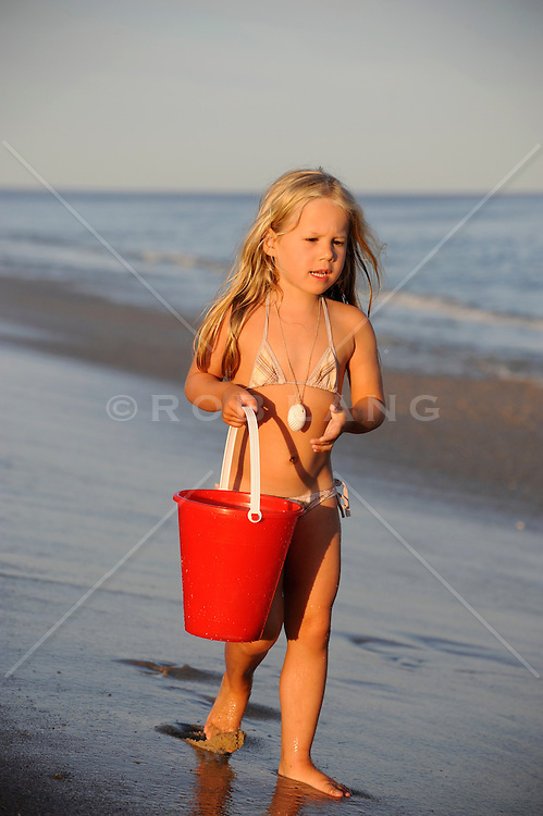 beautiful child walking on the beach with a red beach pail in The Hamptons