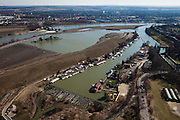 Nederland, Limburg, gemeente Maastricht, 07-03-2010; waterhuishouding van de Maas. De overlaat, onder in beeld voert - bij hoogwater - extra water af om zo de stuw bij Borgharen (l) te ontlasten. Rechts het verbindingskanaal wat leidt naar de Zuid-Willemsvaart. Het eiland Bosscherveld (l) wordt gedeeltelijk afgegraven, de Maas kan bij hoogwater in de toekomst ook over het eiland stromen. De bebouwing van Maastricht aan de horizon..Water management of the Meuse. The spillway (bottom) functions in case of high waters as an extra relieve for the weir at Borgharen (l). On the right the channel which leads to the South Willemsvaart. The island Bosscherveld (l) is partially excavated, in the future the Meuse high water will flow over the island..luchtfoto (toeslag), aerial photo (additional fee required).foto/photo Siebe Swart
