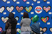 Local residents on the first anniversary of the Grenfell tower block disaster where local schoolchildren have drawn pictures and messages, on 14th June 2018, in London, England. 72 people died when the tower block in the borough of Kensington & Chelsea were killed in what has been called the largest fire since WW2. The 24-storey Grenfell Tower block of public housing flats in North Kensington, West London, United Kingdom. It caused 72 deaths, out of the 293 people in the building, including 2 who escaped and died in hospital. Over 70 were injured and left traumatised. A 72-second national silence was held at midday, also observed across the country, including at government buildings, Parliament.