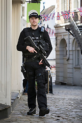 © Licensed to London News Pictures. 17/05/2018. Windsor, UK. Armed police patrol the side streets near Windsor Castle two days ahead of the wedding of Prince Harry and Meghan Markle. Later, a full military procession rehearsal will take place through the streets of Windsor. Photo credit: Peter Macdiarmid/LNP