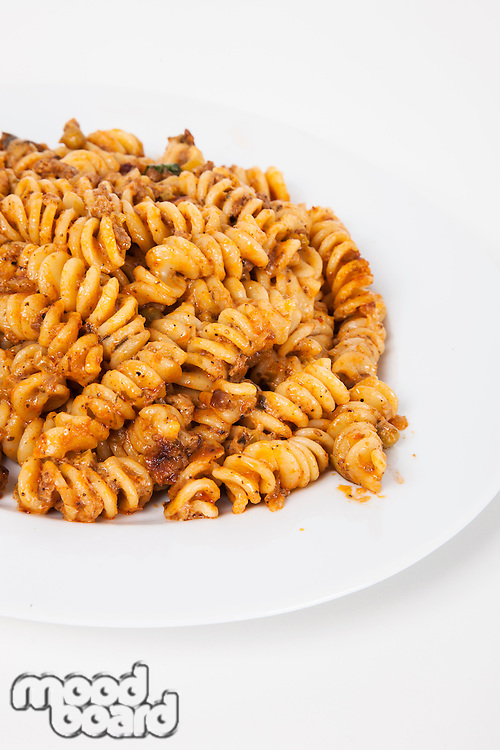Close-up of spicy pasta in plate over white background