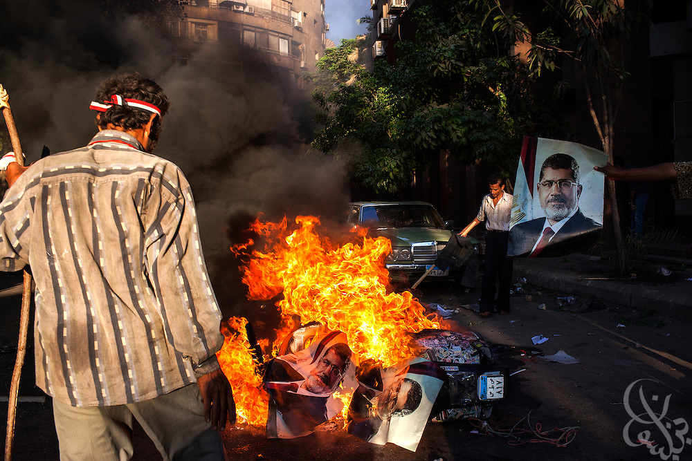Opponents of deposed Egyptian President Mohamed Morsi burn posters of the ex-leader left behind by  Pro-Mosi supporters following violent clashes between the two factions July 22, 2013 in the Garden City district of Cairo, Egypt. Fighting between the two sides broke out near Tahrir Square in the late afternoon, and the subsequent running street battles with rocks and guns  saw at least one killed.