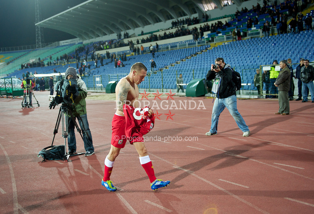 SOFIA, BULGARIA - Tuesday, October 11, 2011: Wales' Craig Bellamy throws his shirt into the travelling supporters after his side's 1-0 victory over Bulgaria during the UEFA Euro 2012 Qualifying Group G match at the Vasil Levski National Stadium. (Pic by David Rawcliffe/Propaganda)