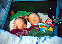 China, Taiyuan, 2008. Oblivious to the teeming shoppers around them, two brothers sleep in a wheeled cart near the Hou Jia Xiang vegetable market.