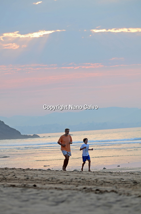 Father and son running on Vega Beach, Asturias