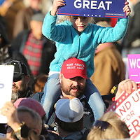 "A young fan of President Trump holds up a ""Keep America Great"" sign as she waits for his arrival Monday afternoon at the Tupelo Regional Airport."