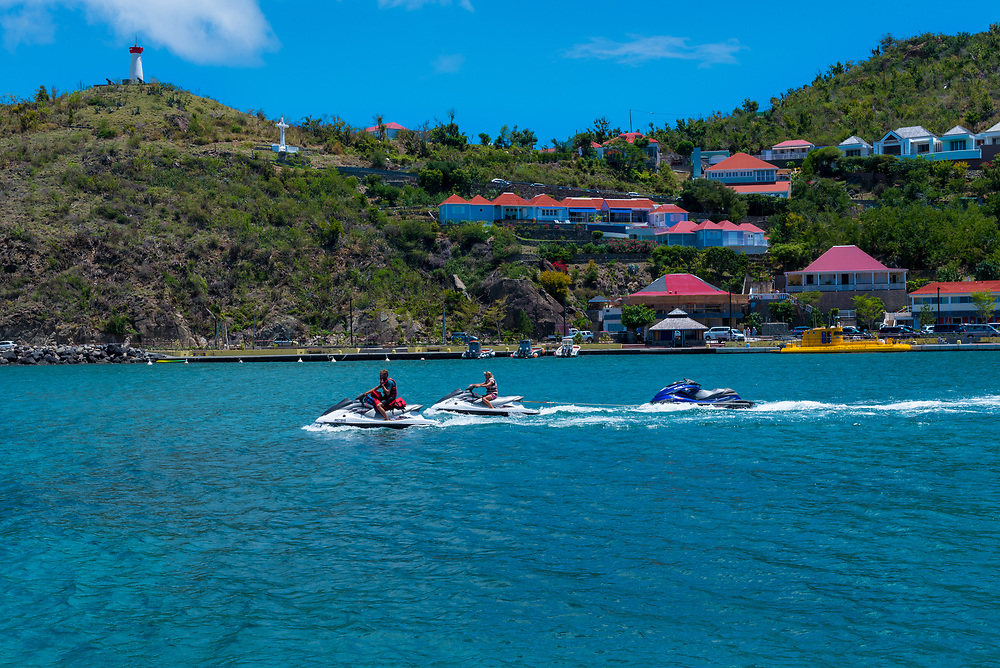 Gustavia, St Barths-- April 25, 2018. Man and woman pilot jet skis in Gustavia while towing an empty one behind them. Editorial Use Only.