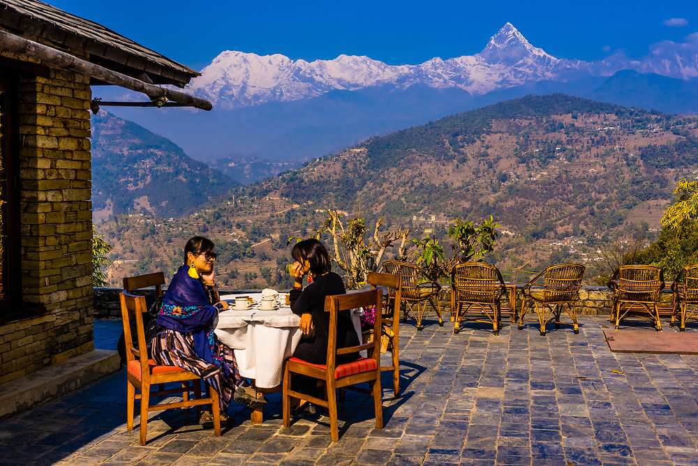Chinese tourists enjoy the view of the peaks of the Annaupurna Massif of the Himalayas from Tiger Mountain Pokhara Lodge, Lekhnath (near Pokhara), Nepal.