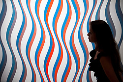 "© Licensed to London News Pictures. 03/09/2013. London, UK. A Sotheby's employee views past ""Image I, Revised White"" (1967) by Bridget Riley during the press view for an exhibition of art from the 1960's at Sotheby's in London today (03/09/2013). The exhibition, entitled ""The New Situation: Art in London in the Sixties"" and located at the auction house's New Bond Street building, is open to the public from 4th to the 11th of September 2013. Photo credit: Matt Cetti-Roberts/LNP"