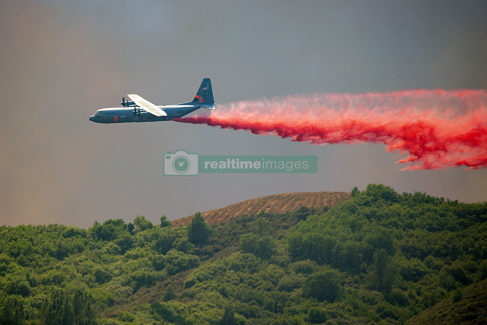 August 1, 2018 - California, U.S. - A C-130 Air Tanker drops fire retardant on a ridge West of Scotts Valley Road near Lakeport, California, to help hold a dozer line attempting to slow the spread of the River Fire burning in Lake and Mendocino Counties. The River Fire is one of two fires making up the Mendocino Complex Fire burning around the west end of Clear Lake. Both fires, the Ranch to the north and the River to the south, are still large and growing. Together they now total 90,912 acres and are still only 24% contained. (Credit Image: © Mark McKenna via ZUMA Wire)