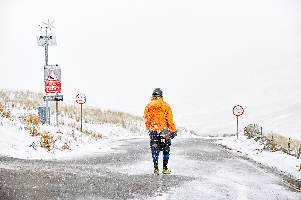 A skateboarder stands at the top of the Struggle, near Kirkstone pass during the beast from the east snow storm, Cumbria, England