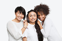 Portrait of young multi-ethnic female friends smiling over white background