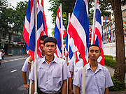 18 NOVEMBER 2015 - BANGKOK, THAILAND:  Thai high school students with Thai flags at the start of the temple's annual fair. Wat Saket is on a man-made hill in the historic section of Bangkok. The temple has golden spire that is 260 feet high which was the highest point in Bangkok for more than 100 years. The temple construction began in the 1800s in the reign of King Rama III and was completed in the reign of King Rama IV. The annual temple fair is held on the 12th lunar month, for nine days around the November full moon. During the fair a red cloth (reminiscent of a monk's robe) is placed around the Golden Mount while the temple grounds hosts Thai traditional theatre, food stalls and traditional shows.     PHOTO BY JACK KURTZ