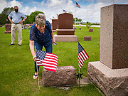 25 MAY 2020 - ROLAND, IOWA: in Roland Cemetery, in Roland, Iowa, a farming community about an hour north of Des Moines. Ritland, a Vietnam era veteran, rode his bicycle about 74 miles through central Iowa to honor veterans buried in cemeteries in rural Iowa. In 2020, most public Memorial Day events in Iowa were canceled because of the COVID-19 pandemic, but some families had their own private events.        PHOTO BY JACK KURTZ
