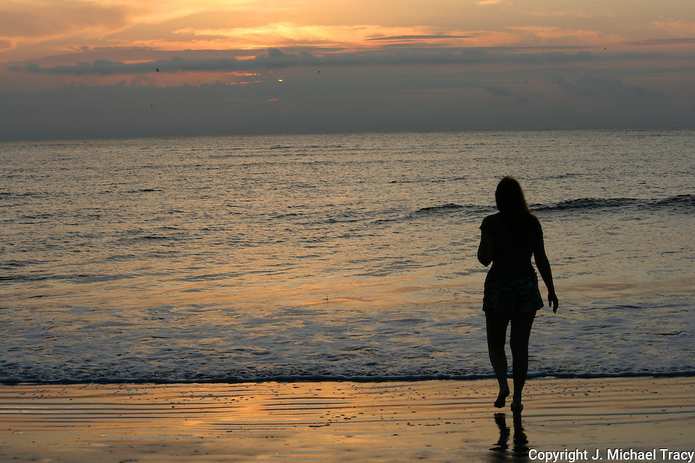 Silhouette of woman walking on a Jekyll Island Beach at sunrise, sunset.