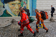 Three emergency medics make their way past a large poster of  the Dutch Impressionist artist Vincent van Gogh at Somerset House where their HEMS Air Ambulance helicopter has landed to help treat a road traffic accident victim in nearby Aldwych, on 15th June 2019, in London, England.