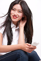 Portrait of cheerful young woman in casuals using mobile phone over white background
