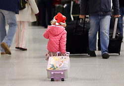 A young girl with a santa hat and suitcase at London Gatwick airport with her family as the Christmas getaway starts Friday, 20th December 2013. Picture by Stephen Lock / i-Images