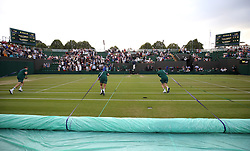 Ground staff pull the covers over court three as rain stops play on day three of the Wimbledon Championships at the All England Lawn Tennis and Croquet Club, Wimbledon.