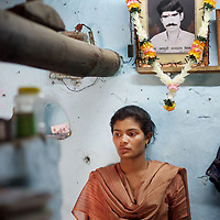 Nanda, age 16, stands beneath a garlanded photograph of her father Kadu, a cotton farmer who committed suicide by swallowing pesticide on February 29th 2006. Kadu had fallen into debt and could not keep up repayments on a loan of INR59,000 (£740) which, with interest had risen to INR100,000 (£1250). Kadu left a wife and four children. His daughter, Nanda was hoping to go on to college but will now have to give up school in order to work on the family farm.<br />