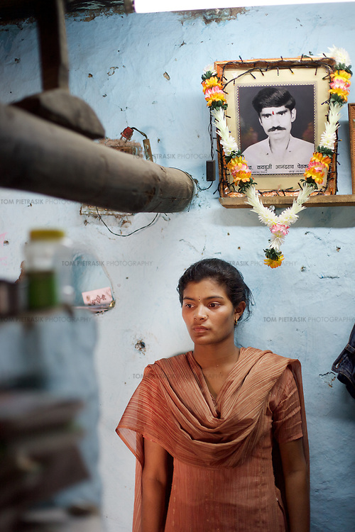 """Nanda, age 16, stands beneath a garlanded photograph of her father Kadu, a cotton farmer who committed suicide by swallowing pesticide on February 29th 2006. Kadu had fallen into debt and could not keep up repayments on a loan of INR59,000 (£740) which, with interest had risen to INR100,000 (£1250). Kadu left a wife and four children. His daughter, Nanda was hoping to go on to college but will now have to give up school in order to work on the family farm.<br /> <br /> Since June 2005, more than 300 farmers from the Vidarbha """"Cotton Belt"""" in Maharashtra, have committed suicide. These farmers suffered spiraling debt as a result of India's trade liberalisation. Until last year, the Indian government offered Vidarbha's farmers a minimum price for their cotton of INR2500 (£31.25) per quintal. This figure has now dropped to INR1700 (£21.25). Indian cotton farmers are now forced to compete on the open market with farmers in the US and Europe who are provided billions of dollars worth of subsidy. In addition to the fall in the price of cotton, Vidarbha's farmers have also had to absorb a rise in the price of deisel and pesticide. In an attempt to draw attention to their plight, whole villages in this eastern district of Maharashtra, have put up their land for sale. Others have been threatening to sell their kidney's to ease their debt. <br /> <br /> Photo: Tom Pietrasik<br /> Maharashra, India<br /> March 20th 2006"""