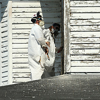 Shon Grant and Vernon Brown, employees with Mask Construction Services out of Tupelo, work on scraping off the old lead base paint from the Spain home as they prep it for new paint on Friday in Tupelo.
