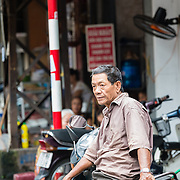 Vietnamese motor taxi driver leaning on his bike while waiting for a fare