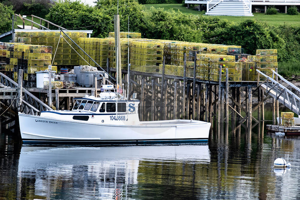 A lobster boat tied up to a wharf piled high with lobster traps in New Harbor, Maine. The tiny picturesque pocket harbor is one of the last working harbors on the midcoast along the Pemaquid Peninsula