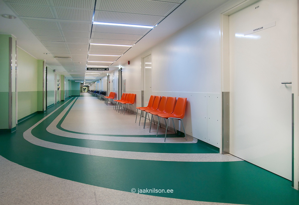 Tartu university hospital waiting area and corridor. Green and white flooring. Orange chairs in rows against the wall.