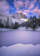 The Lago Bleu is a very small lake lying right a the feet of what is probably the most photogenic mountain in the world. The Cervino, better known as Matterhorn outside Italy, is only the third highest peak in the Alps, but certainly the most famous thanks to its unmistakable look..I took this picture on a evening of early November at sunset, along with the first clearing after five days of unceasing snowfalls. .Since I noticed that the clouds were moving fast, I opted for a very long exposure (80 seconds) confident that this choice would have produced some beautiful motion blur in the sky. .The amazing, very unusual texture on the lake surface is probably due to the fact that the lake was not completely frozen when the snow began to fall.