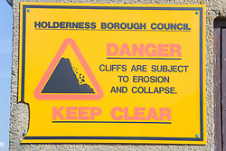 Sign warning of cliff erosion at Kilnsea; East Yorkshire; England,