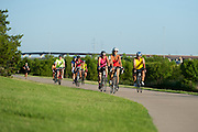 """Mayor Laura Maczka of Richardson (red) and Mayor Oscar Trevino of North Richland Hills (yellow) lead the group during the first  """"Elected Officials bike ride"""" along the Champion Trail in Irving, Texas on August 6, 2013. Riders included nearly 15 mayors and council members from around north Texas with the aim to promote biking in their neighborhoods. (Cooper Neill / Texas Tribune)"""
