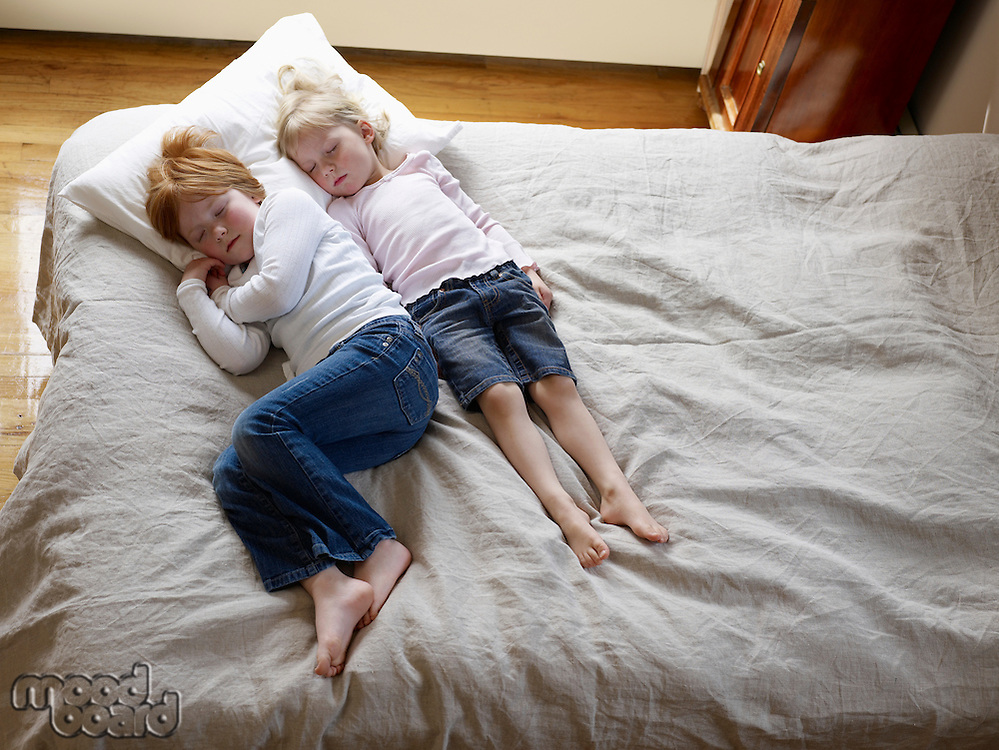 Two sisters lie sleeping on a bed elevated view
