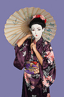 Portrait of Japanese woman in kimono with painted face holding parasol against purple background