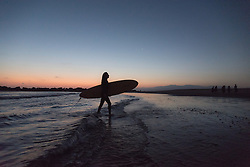 Michelle Ivanoff heads back in after catching some waves  in Venice Beach, California October 9, 2014. (Photo by Ami Vitale)