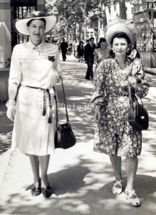 two fashionable dressed adult woman strolling on a sunny day France 1945