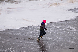 © Licensed to London News Pictures. 27/12/2017. Aberystwyth, UK. As the wind picks up strength, and blows  bitterly cold air in from the north, a young boy plays a risky game of 'dodging the waves' on the beach at Aberystwyth on the west Wales coast .Photo credit: Keith Morris/LNP