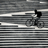 A man riding his bike up the stairs at Robson Square in Vancouver Canada.