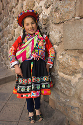 South America, Peru, Cuzco, girl in traditional clothing by stone wall