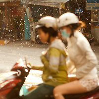 Two women on a moped in Ho Chi Minh City, Vietnam. I was sheltering under a shop canopy in the torrential rain and which focusing on the road, these two sped past and I captured them by mistake. Quite liked the result, though! - Travel photography prints by Peter Jackson -