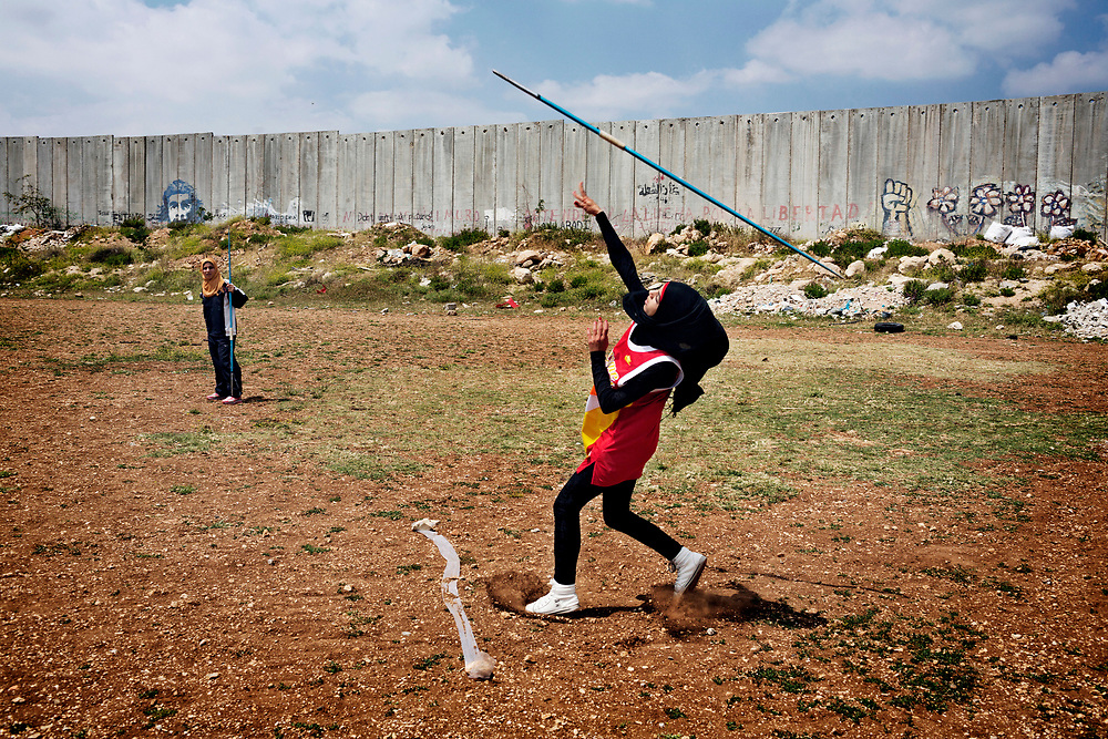 Students from the Al-Quds University javelin team wrap up the last practice before summer vacation in the West Bank city of Abu Dis, next to the Israeli Separation Wall.