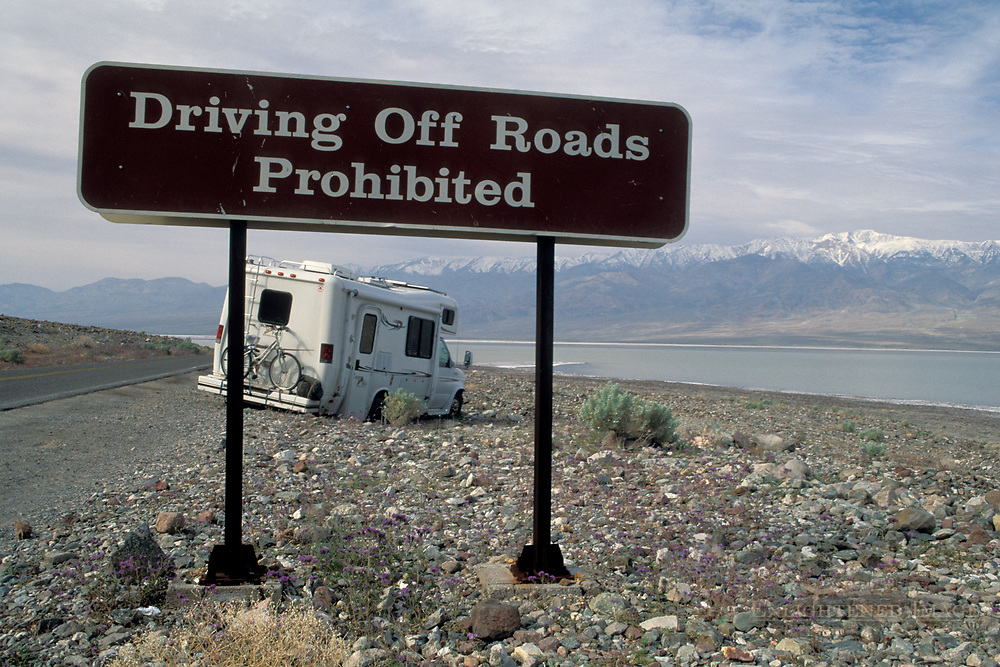 Driving off road prohibited Tourist RV tavel Camper stuck in desert rocks after drive offroad next to warning sign, near Badwater, Death Valley National Park, California