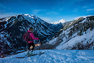 After skinning up Buttermilk Mountain a skier looks out at Pyramid Peak in the moonlight in Aspen, Colorado.
