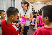 31 MARCH 2013 - BANGKOK, THAILAND:     Michelle Kao helps children put up decorations before Easter services at the Thai Peace Foundation office in the Bangkapi section of Bangkok.     PHOTO BY JACK KURTZ
